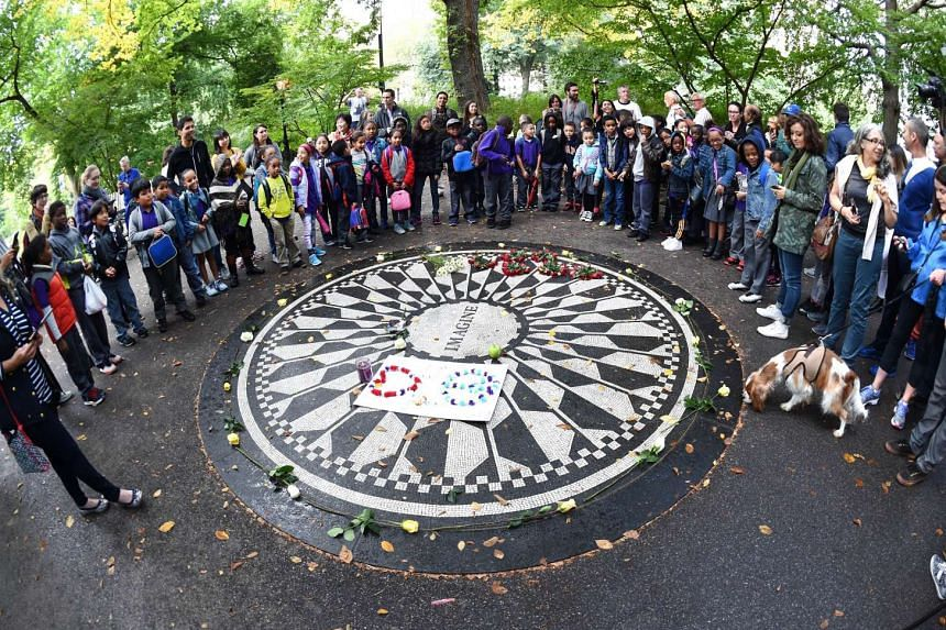 Fans gather at the Imagine mosaic plaque in the Strawberry Fields section of Central Park, in New York, on Oct 9, 2015.