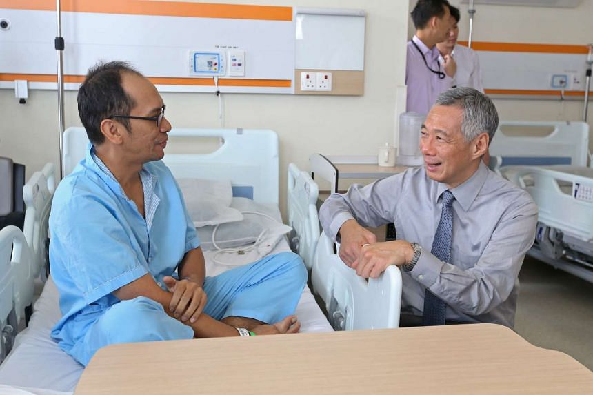 PM Lee Hsien Loong visits patients including (left) Rais bin Misran, 37, after the official opening of the Ng Teng Fong General Hospital and Jurong Community Hospital.