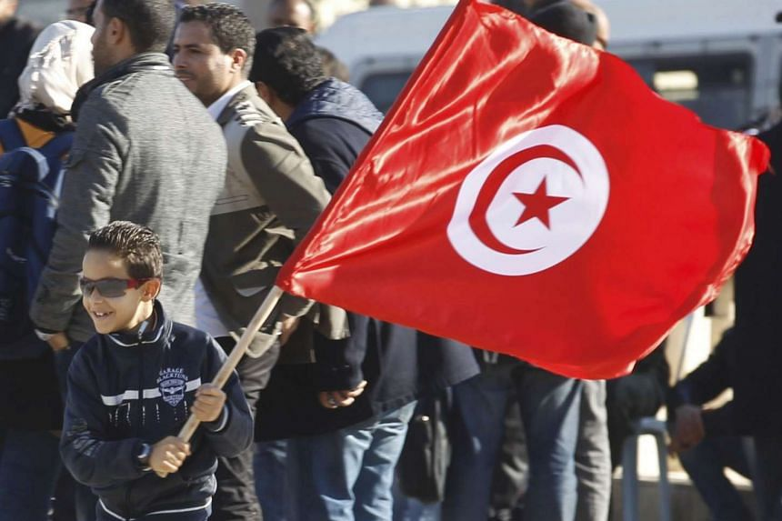 A Tunisian boy waving a flag as he runs during a rally to mark the third anniversary of the Tunisian revolution in Tunis, in this on Dec 17, 2013, file photograph.