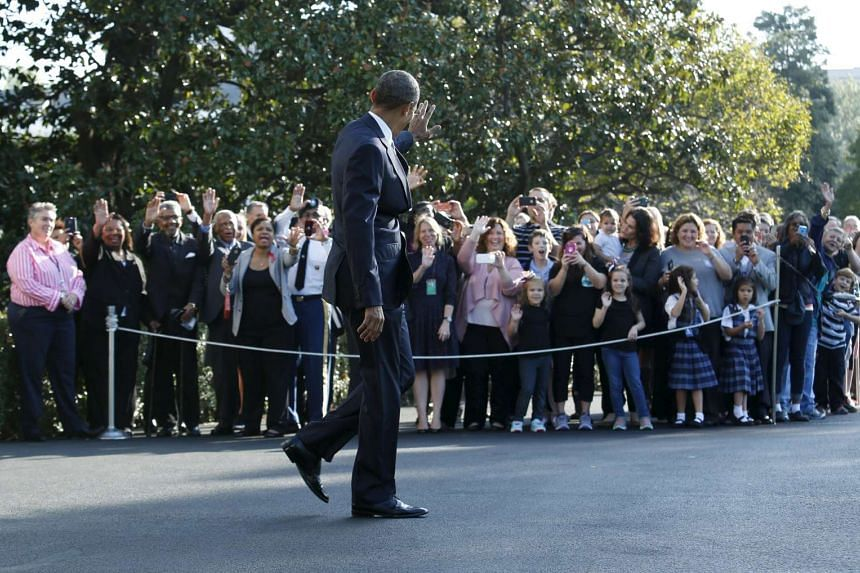US President Barack Obama waves to visitors as he walks out from the White House in Washington before his departure to Roseburg, Oregon.