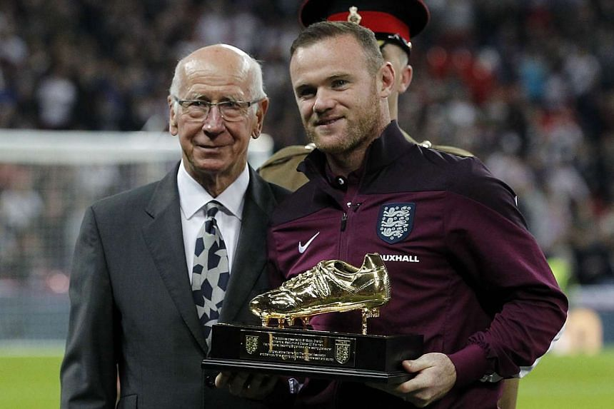 Rooney with Sir Bobby Charlton, who presented him with the golden boot.