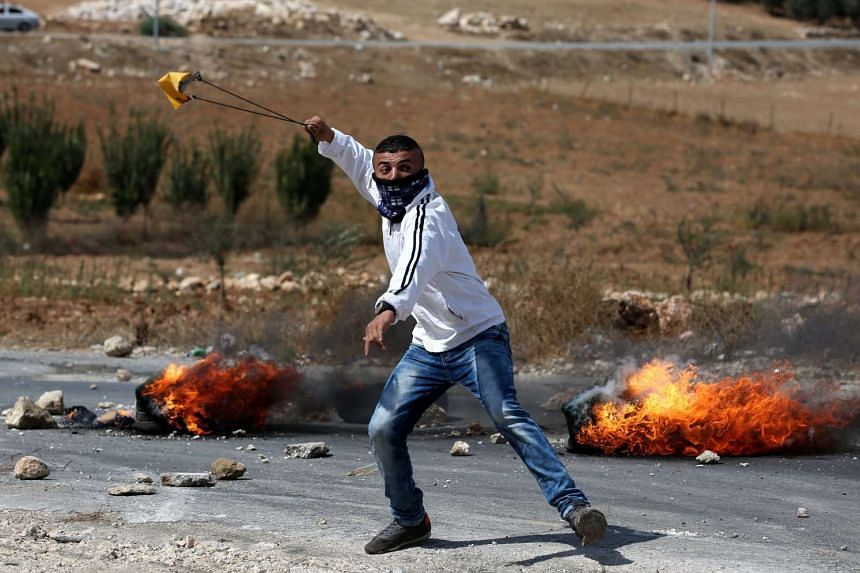A Palestinian protester throwing stones during clashes with Israeli troops in the West Bank city of Hebron on Thursday. Israeli leader Benjamin Netanyahu has pledged a tough response to a fresh wave of Palestinian violence.