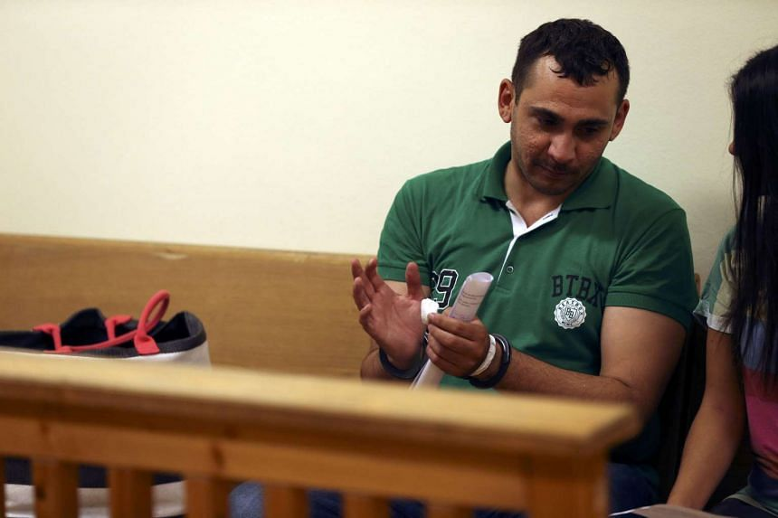 A migrant gestures as he talks with his translator as he appears in front of a court in Szeged, Hungary.