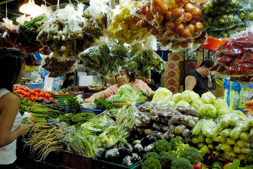 A shopper bargains with a vegetable seller at a wet market in Singapore.