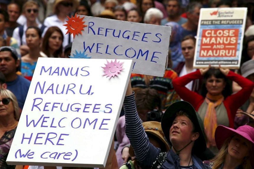 Demonstrators hold aloft placards during a rally in support of refugees that was part of a national campaign in central Sydney, Australia, on Oct 11, 2015.