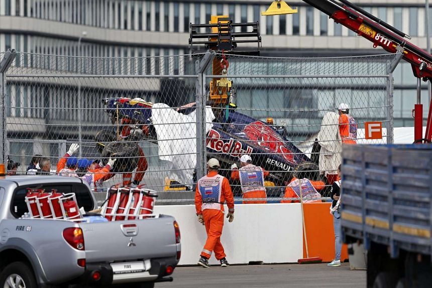 Marshals load the damaged car of Spanish Formula One driver Carlos Sainz of Scuderia Toro Rosso after he crashed during the third practice session at the Sochi Autodrom circuit, in Sochi, Russia, on Oct 10, 2015.