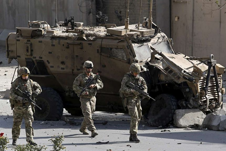 Nato soldiers walk in front of a damaged military vehicle at the site of a suicide car bomb blast in Kabul, Afghanistan, on Oct 11, 2015.