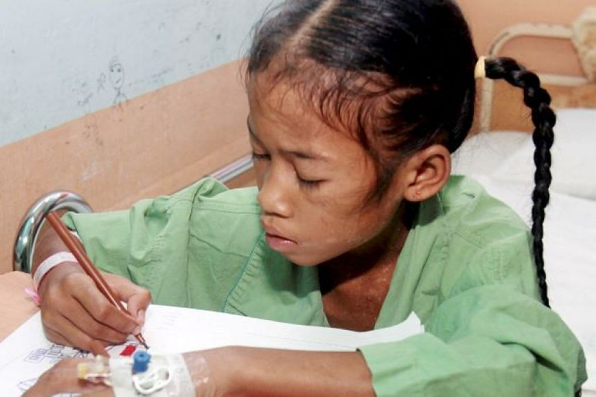 Norieen Yaakob sitting up and colouring at Hospital Raja Perempuan Zainab II. Both Norieen and another Orang Asli girl, Miksudiar Aluj, had survived in the jungle for 40 days without food.