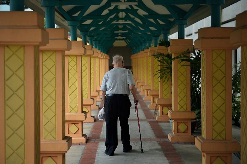 An elderly man walking along a covered walkway in Toa Payoh.