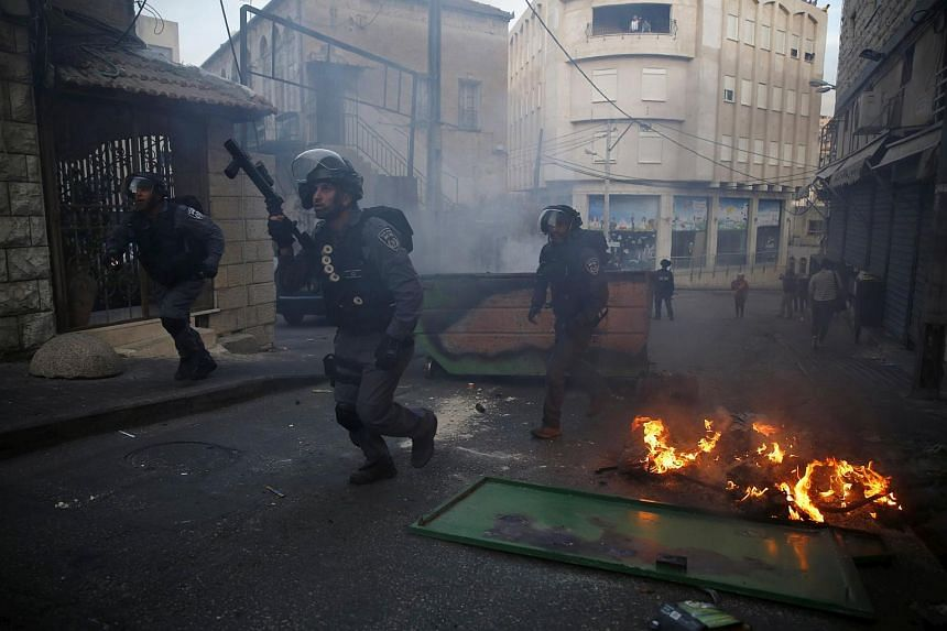 Israel policemen run in a street in during clashes with Israeli Arabs in Nazareth at northern Israel, on Oct 10, 2015.