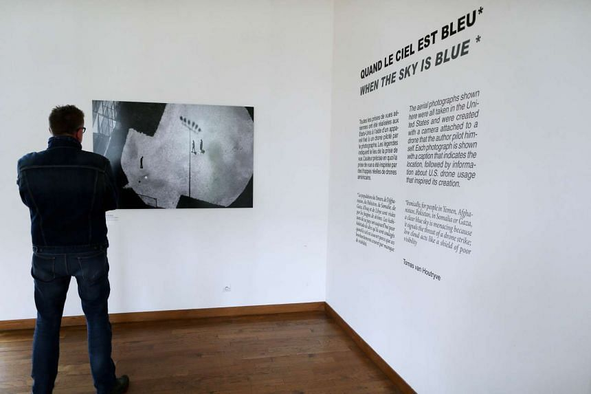 """A man looks at a photograph by Belgian Thomas van Houtryve at the """"When the sky is blue"""" exhibition on October 5, 2015 in Bayeux, northwestern France, as part of the 22nd edition of the Bayeux-Calvados award for war correspondents."""