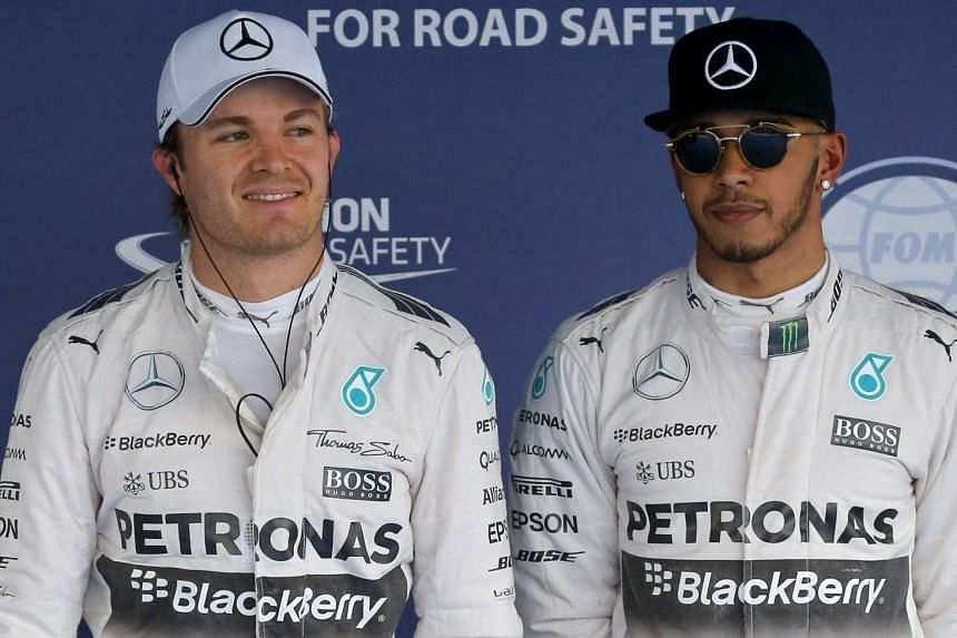 Mercedes Formula One driver Nico Rosberg of Germany and his team mate Lewis Hamilton (R) of Britain, celebrate after qualified for the pole and second position respectively for the Russian F1 Grand Prix in Sochi, Russia Oct 10, 2015.