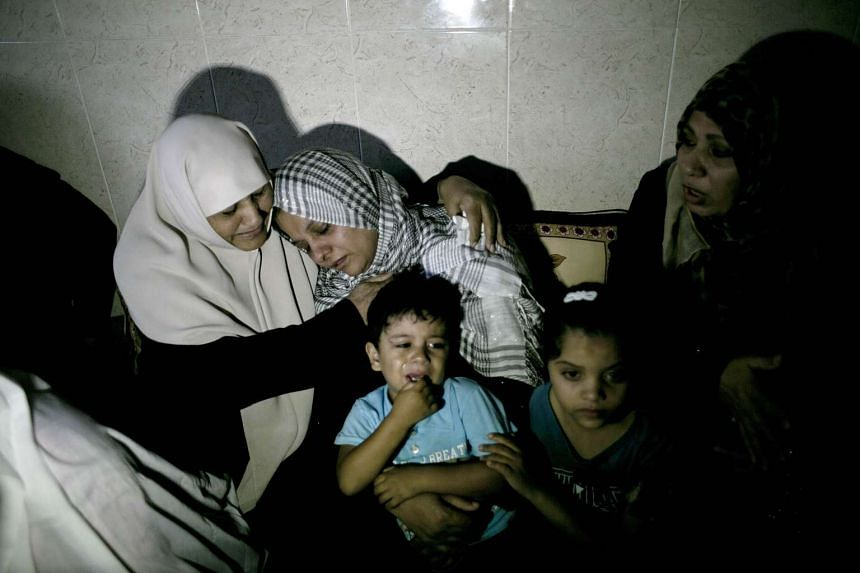 The mother (centre) of Palestinian Khalil Othman, 15, who was killed in clashes with Israeli forces east of Khan Yunis, on Oct 10, 2015 mourns with relatives at the family's home in Khan Yunis, in the southern Gaza Strip.