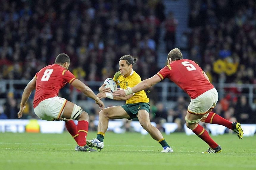 Australia's Matt Toomua (centre) in action against Wales' Taulupe Tipuric (left) and Alun Wyn Jones (right) during the Rugby World Cup 2015 pool A match between Australia and Wales at Twickenham stadium, in London, Britain, on Oct 10, 2015.