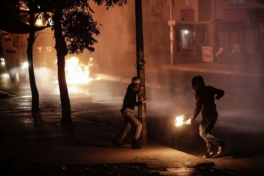 Protesters throw molotov cocktails towards a water cannon during clashes with police on October 10, 2015 at the gazi district in Istanbul, few hours after the deadly attack in Ankara.