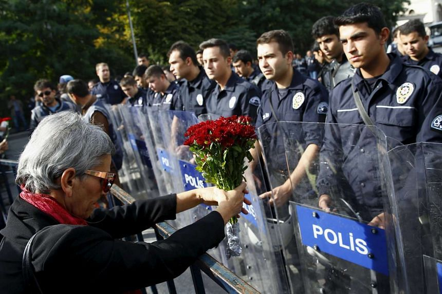 A demonstrator holds flowers before a police barricade during a commemoration for the victims of Saturday's bomb blasts in the Turkish capital, in Ankara, Turkey, on Oct 11, 2015. Turkish investigators worked on Sunday to identify the perpetrators an
