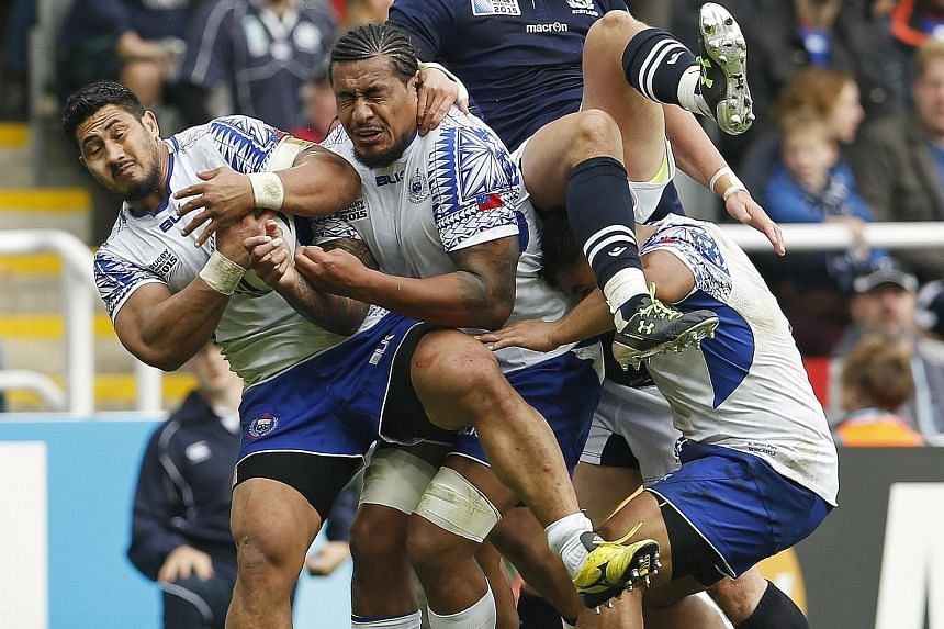Samoa's Alafoti Fa'osiliva (far left) shielding the ball from Scotland during their Rugby World Cup clash in Newcastle yesterday. Scotland won 36-33 to advance to the quarter-finals as Pool B runners-up, at the same time eliminating Japan even though