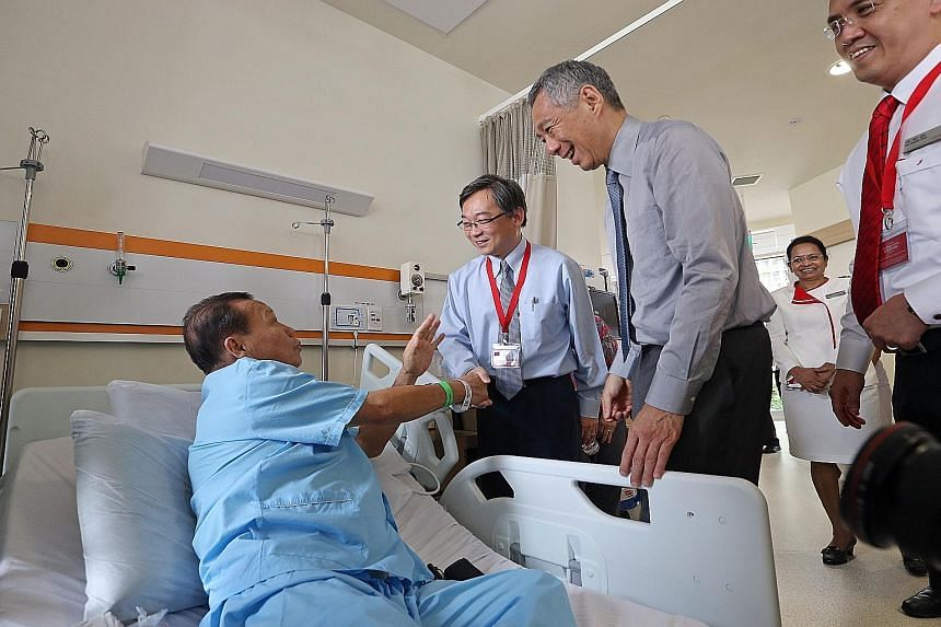 Prime Minister Lee Hsien Loong and Health Minister Gan Kim Yong visited patients, including Mr Chionh Koek, 62 (above), at the Ng Teng Fong General Hospital yesterday. Mr Lee spent about two hours touring the hospital and the adjoining 400-bed Jurong