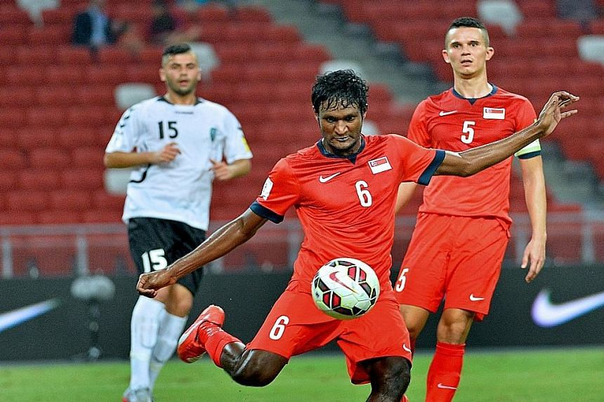 Madhu Mohana clears the ball while Baihakki Khaizan keeps a close watch as the central defenders help Singapore earn a crucial 1-0 win over Afghanistan in a Group E World Cup qualifier.
