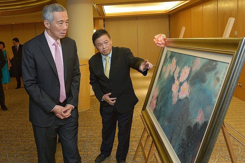 Guest of honour, Prime Minister Lee Hsien Loong, with Sin Hua Gallery owner Chan Kok Hua, who donated the painting Glorious Lotuses, by Beijing artist Liu Yanshui, for the Singapore Chinese Orchestra's fund-raiser on Friday night.