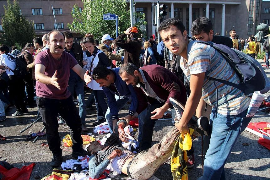 After the double explosions outside Ankara's main train station, bodies covered by flags and banners, including those of the pro-Kurdish opposition Peoples' Democratic Party (HDP), lay scattered on the road among bloodstains and body parts.