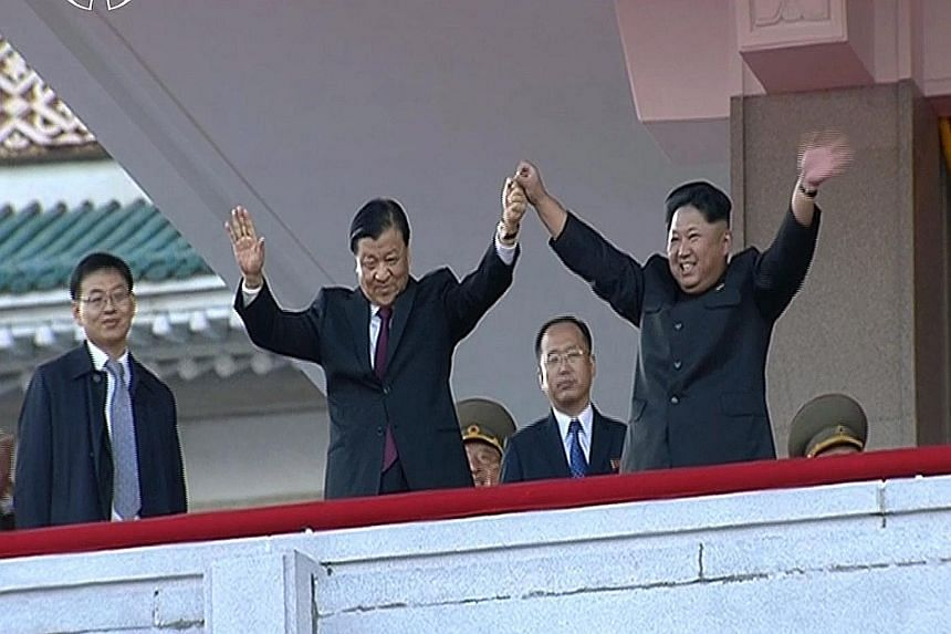 North Korean leader Kim Jong Un (right) holding hands with senior Chinese Communist Party official Liu Yunshan during the massive military parade in Pyongyang yesterday.