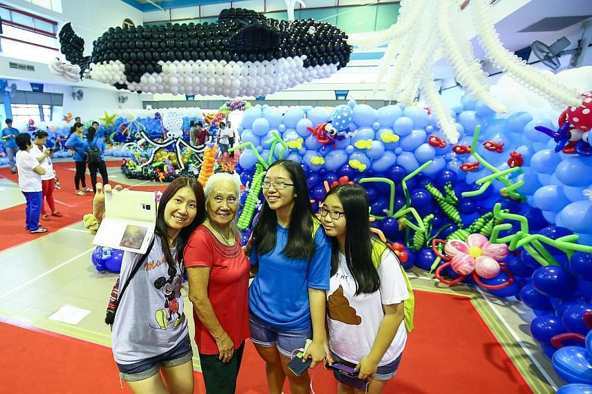 Madam Tham Lai Cheng, 77, her daughter Khwong Siew Fong, 50, and grandchildren Glenda Ong, 16, and Artemis Ong, 13, posing for a photo at the Balloon Underwater World event at Chua Chu Kang Community Club yesterday. A 10m-long whale sculpture was the
