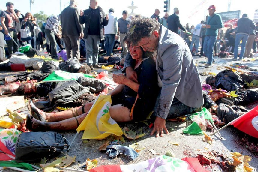 An injured woman is comforted at the scene of the blasts.