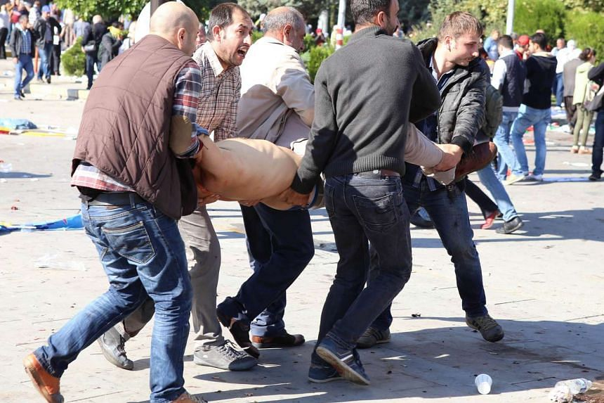 People carry away a victim from the scene of the blasts.