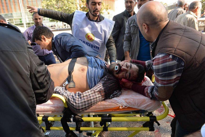 An injured man is wheeled away on a stretcher.