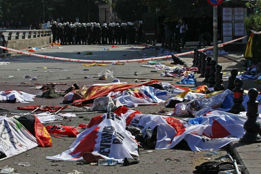 Turkish riot police forces secure the site, as victims' bodies on the street are covered with banners and flags.