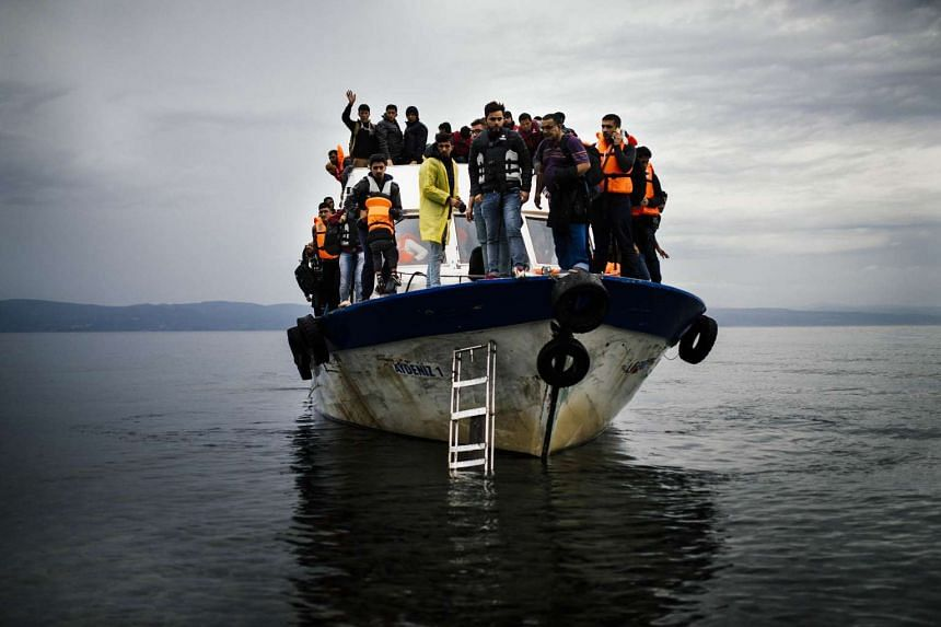 Refugees and migrants arrive by boat on the Greek island of Lesbos after crossing the Aegean sea on Oct 11, 2015.