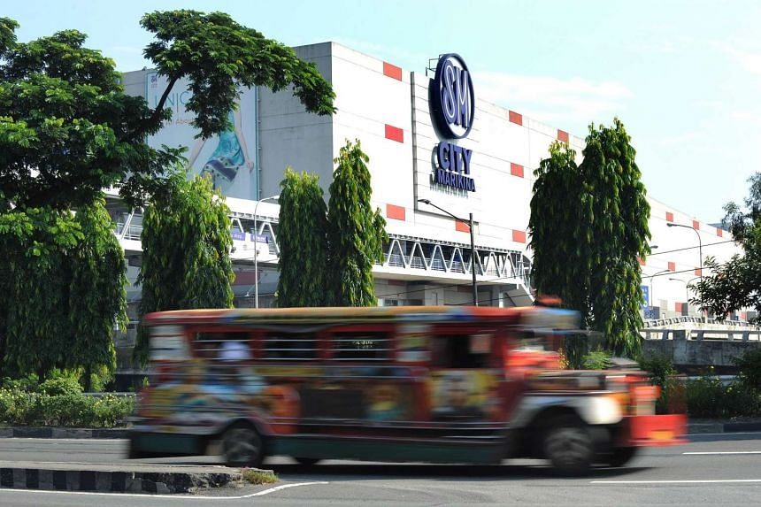 Traffic passes by a mall run by SM, the largest shopping mall and retail operator in the Philippines, in suburban Manila, on Oct 11, 2015.