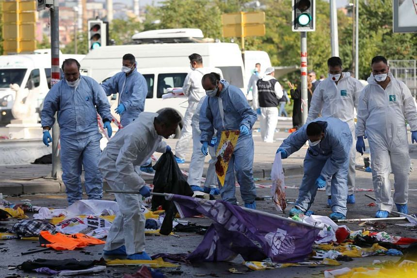 Members of a police forensic team gather evidence at the site.