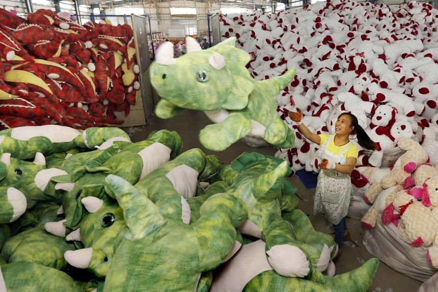 A Chinese worker stacking soft toys at a factory before packing them for export, in Lianyungang, China's Jiangsu province on Sept 6, 2015.