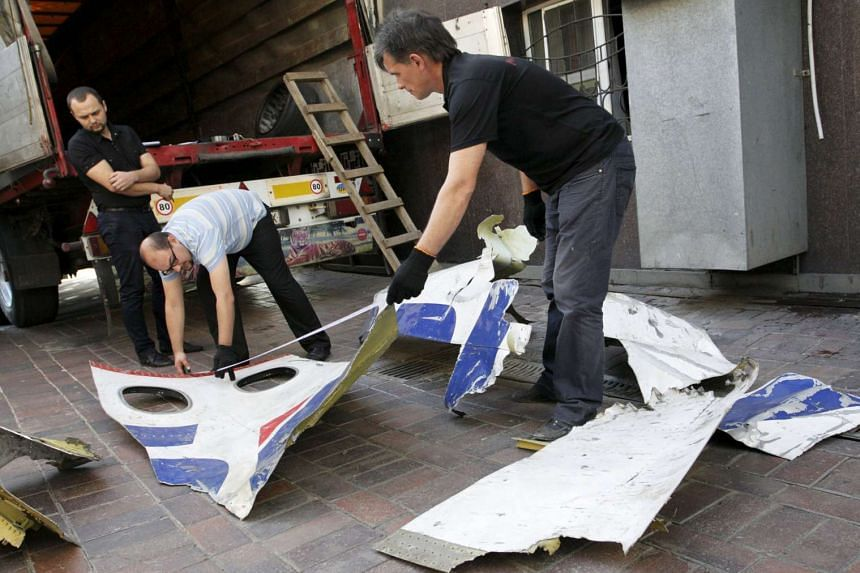 Local workers load pieces of wreckage from a Malaysia Airlines flight MH17, onto a truck outside the Prosecutor General's office in Donetsk, Ukraine, September 30, 2015.