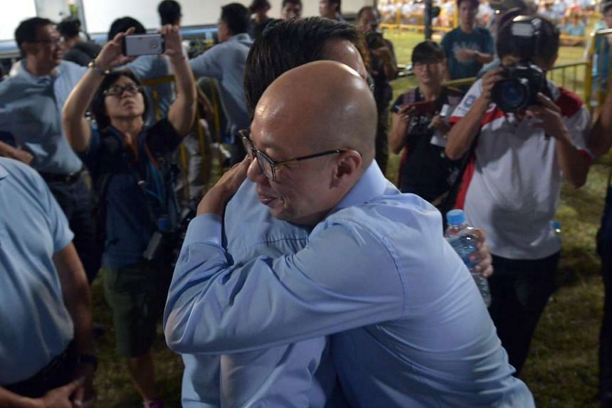 Winner and losers: Workers' Party candidate Terence Tan (Marine Parade GRC) giving Mr Ron Tan (Nee Soon GRC) a hug at the Hougang Stadium before the results of their defeat were announced on Polling Day.