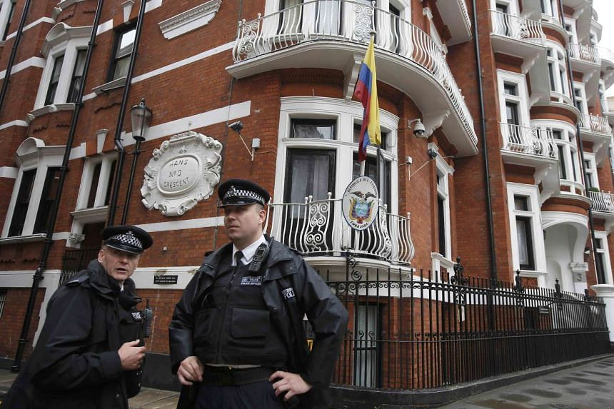 Police officers stand outside the Ecuadorian embassy in London, Aug 13, 2015.