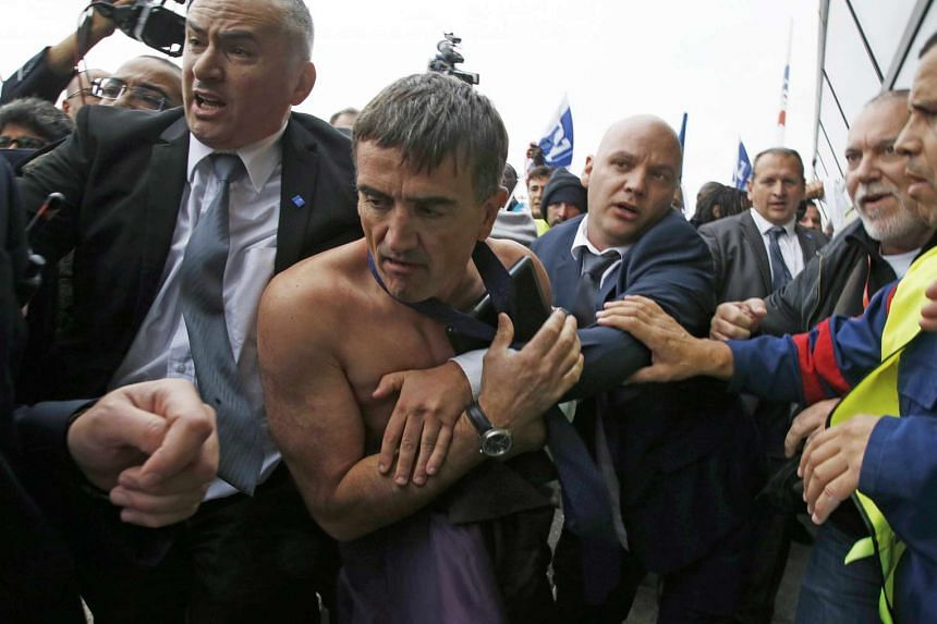 The four Air France employees were arrested part of the investigation into violent scenes which saw one of the struggling airline's executives having his shirt ripped off and scaling a fence.