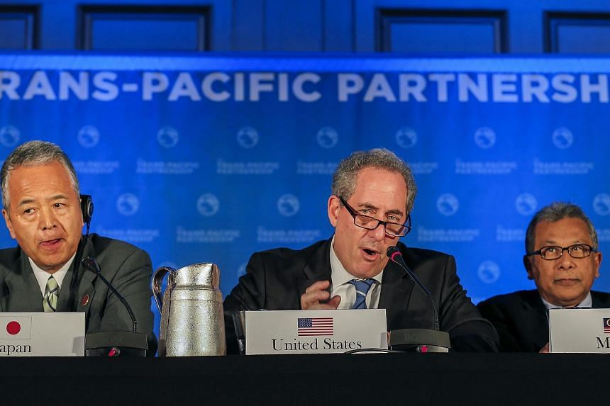 United States Trade Representative Michael Froman (center) is flanked by Japan's Trade Minister Akira Amari (left) and Malaysia's Trade Minister Mustapa Mohamed (right) as he speaks during the closing press conference after an agreement was reached b