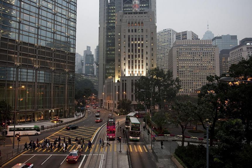 Traffic stops at a light as pedestrians cross the street in the central district of Hong Kong, China, on Jan 5, 2011.