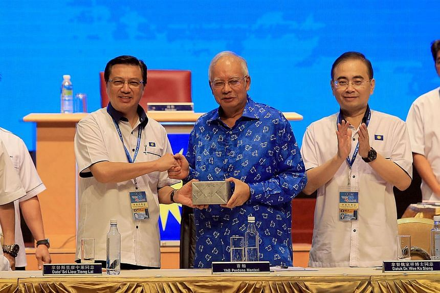 Malaysian PM Najib Razak (centre in blue) receiving a gift from MCA president Liow Tiong Lai at the party's general assembly yesterday.