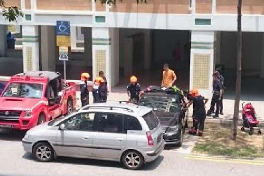 SCDF officers and the baby girl's parents huddled around the black car.