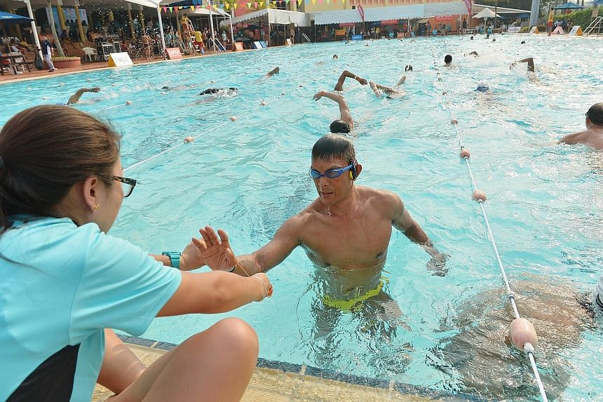 Mr Vincent Koh getting a rubber band from an official to help him keep track of the number of laps swum in the three-day Swim for Hope event yesterday. A total of 1,700 swimmers raised $79,038 for four beneficiaries: Aquatics Heart and Hope, Communit