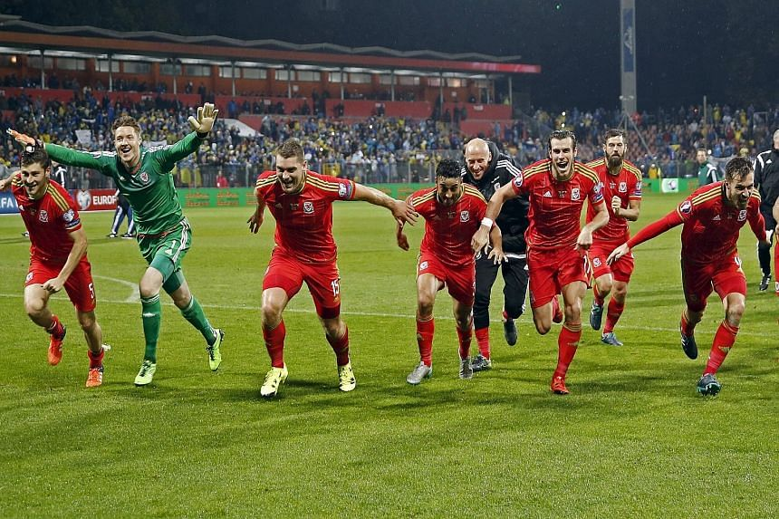 Wales captain and Real Madrid star Gareth Bale (third from right) and team-mates celebrating after they qualified for Euro 2016 - their first major Finals since the 1958 World Cup.