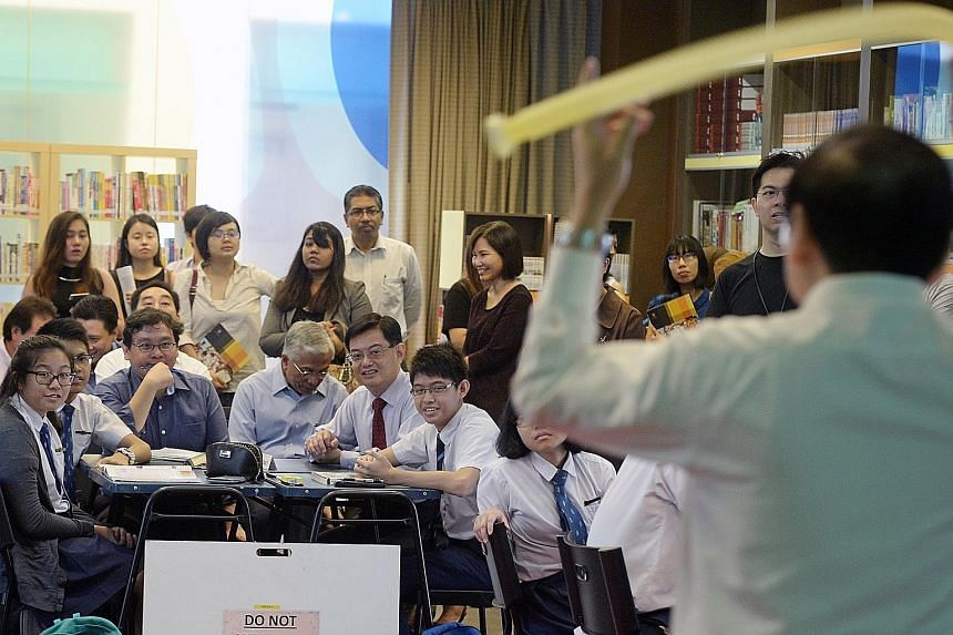 Former Education Minister Heng Swee Keat (with red tie) with students at a physics class during a school tour last month. Many educators have praised his contributions to the sector.