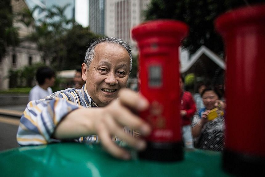 A man placing a toy British colonial-era postbox souvenir on top of a postbox from the colonial period during a protest in the Central district of Hong Kong on Saturday. Hong Kong's red colonial postboxes were painted green after the city reverted to