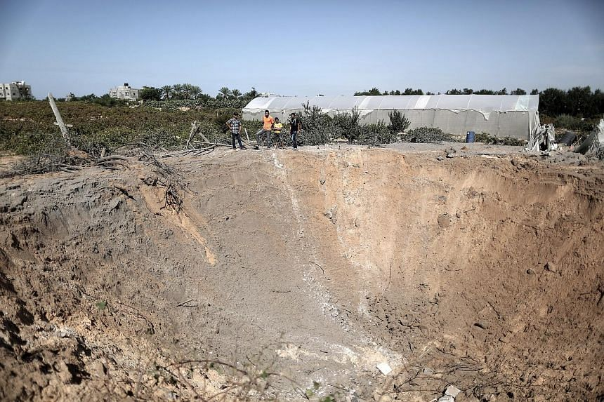 A crater created by an Israeli air strike in the Gaza Strip yesterday. The Israeli military said it had targeted two Hamas weapon sites.