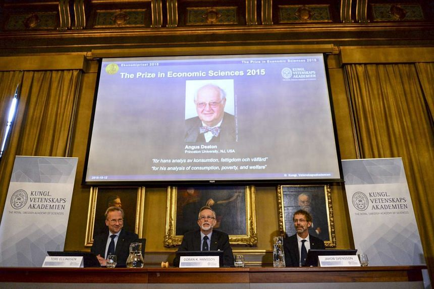 A picture of British economist Angus Deaton, winner of the 2015 economics Nobel Prize, is seen on a screen as Goran K. Hansson (C), permanent secretary for the Royal Swedish Academy of Sciences, and Tore Ellingsen (L), chairman of the prize committee