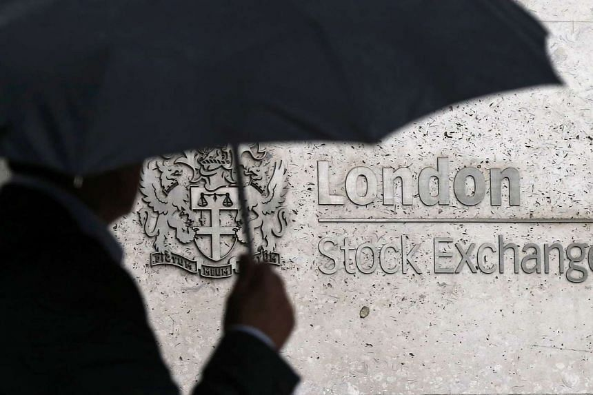 A man shelters under an umbrella as he walks past the London Stock Exchange in London, Britain on Aug 24, 2015.